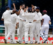 Teammates surround India's bowler Ishant Sharma, third from right, to celebrate the dismissal of West Indies' Leon Johnson during day one of their fourth cricket Test match at Queen's Park Oval in Port-of-Spain, Trinidad, Thursday, Aug. 18, 2016. (AP Photo/Ricardo Mazalan)